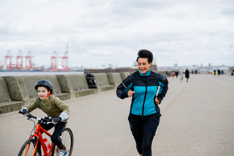 Adult running alongside a young child riding a bike on New Brighton promenade