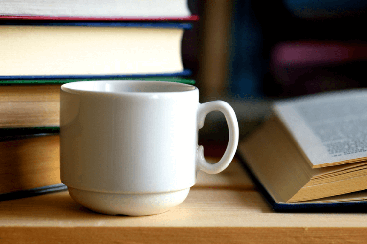 Image of coffee cup in front of a pile of books.