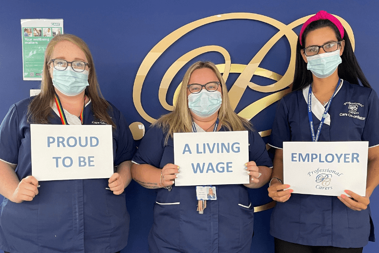A picture of three care coordinators, each holding up a sign that collectively reads up 'Proud to be a living wage employer'. The care coordinators are all wearing face masks.