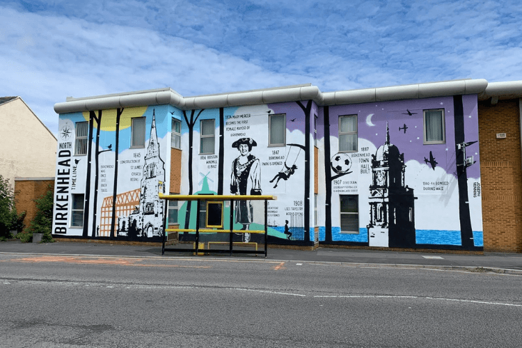 A picture of a vibrant mural depicting scenes from North birkenhead's history, on the side of St James Centre on Laird Street.