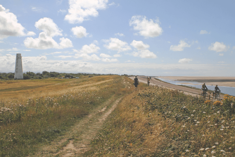 Sunny image of North Wirral Country Park, including leasowe lighthouse. The coast is visible and there are a few cyclists and walkers in shot.