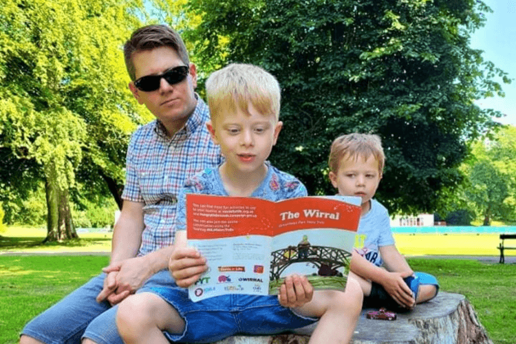 A picture of a father with two young sons in Birkenhead Park ready from a trail booklet, sitting on a tree stump.
