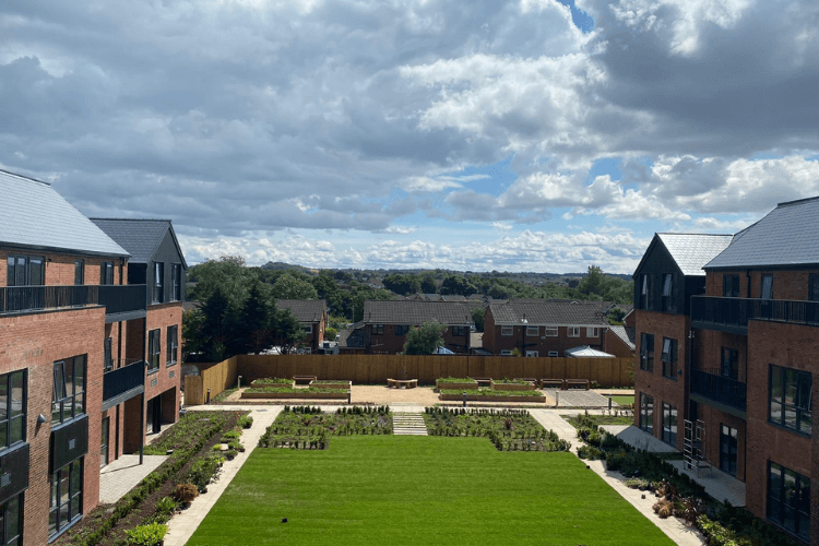 Picture of new extra care development in Saughall Massive from outside, two modern buildings either side of a green lawn.