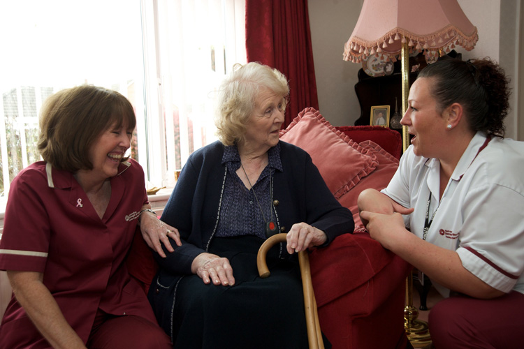 older woman talking to care workers at home