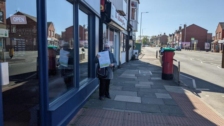 Person stood in Wallasey Village holding the clean air day posters and delivering them to local businesses.
