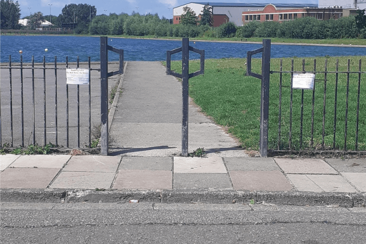 Picture of the entrance to the Boating Lake at Gautby Road. The fencing has signs attached warning people about the blue-green algae and asking them not to use the water.