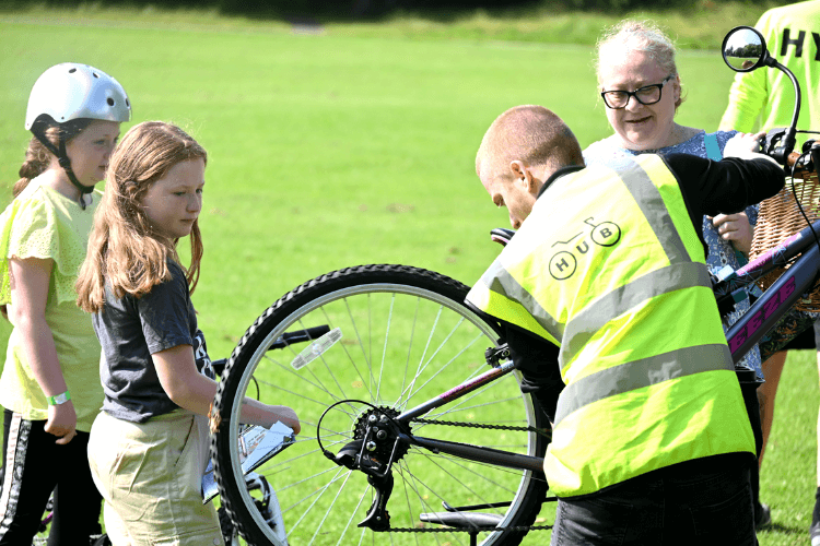 Adult doing a bike safety check on a bike whilst two children look at what he is doing and get advice on how to look after their bike.