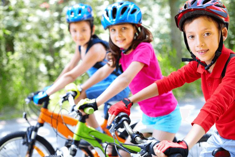 Three children on bikes reading for a bike ride