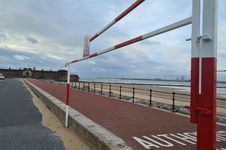 Front of the car park at Fort Perch Rock with a white and red barrier currently locked in the open position.