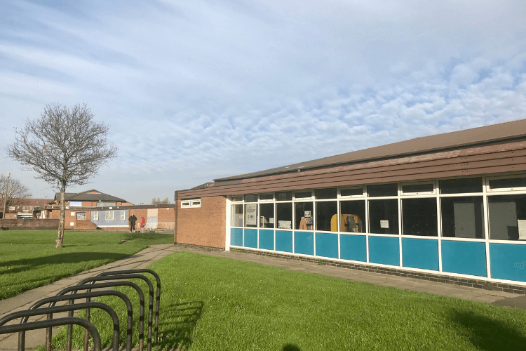 The exterior of Moreton Library. The side of the building is in view with grass and some bike storage in the foreground.