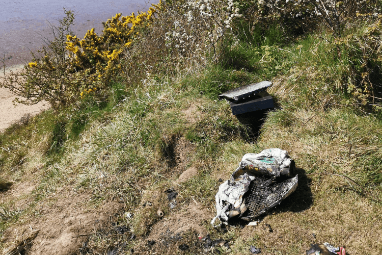 Discarded and burnt disposable barbecue at Thurstaston cliffs.