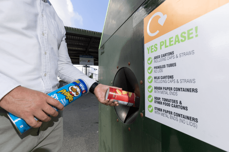 Pringle cans being put in a recycling container