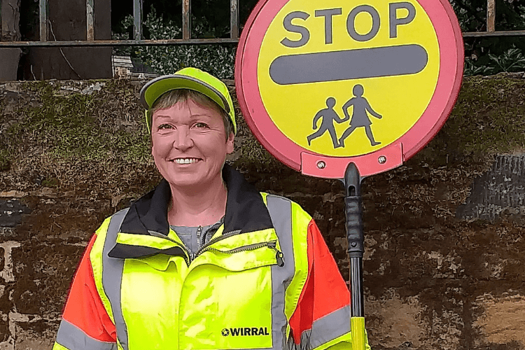 A School Crossing Patrol officer in uniform holding the stop sign that they use to help people to cross the road.