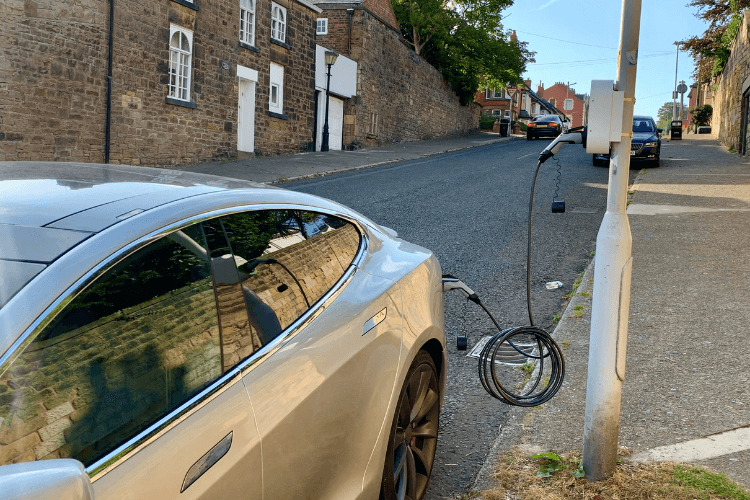 A vehicle plugged into one of the electric vehicle charging points. The car is parked up on the street and the charging wire is attached to the car at one end and to the electric vehicle charging point, which is positioned on the streetlight at the other end.