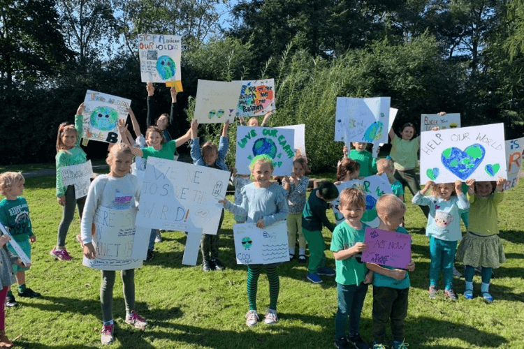 Group of school children holding signs that they have designed as part of previous climate change work with Edsential.