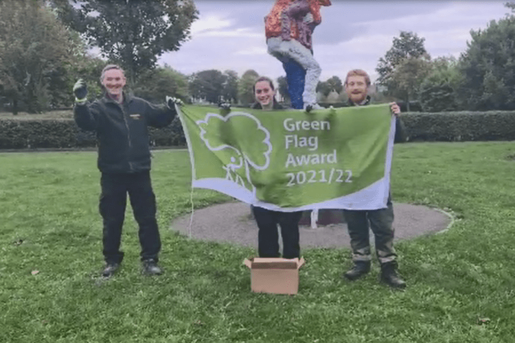 Three of the parks and countryside staff holding up a Green Flag at Queens Park