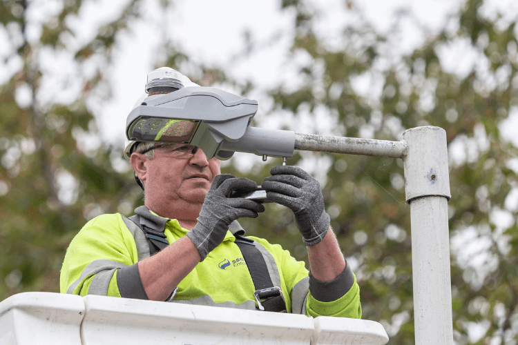 Close up of a streetlight engineer fixing a new LED lamp to the top of a streetlight