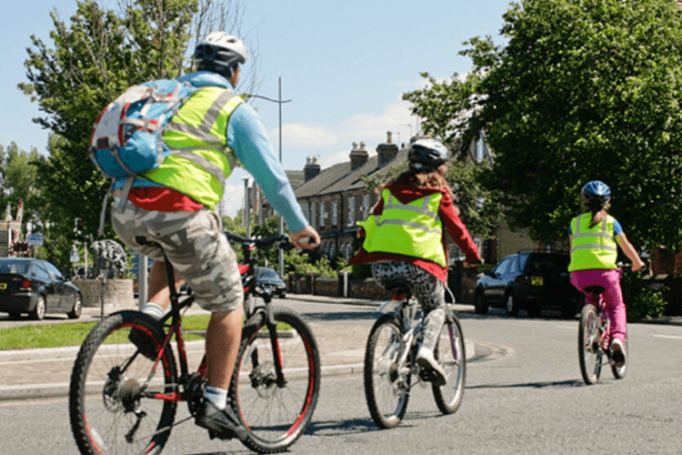 Adult and two children riding bikes with helmets and high vis jackets on.