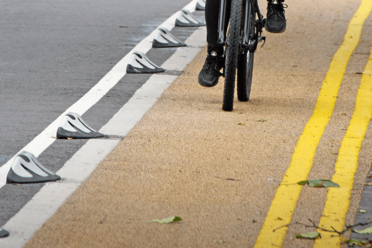 Bike usng the cycle lane and the segregation features, named 'orcas', can be seen marking the edge of the cycle lane.