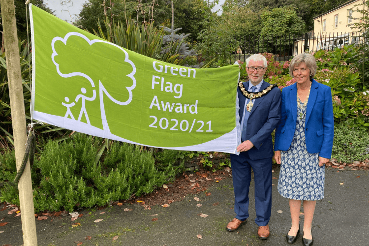 The Mayor of Wirral, Councillor Tony Smith and the Mayoress of Wirral, Barbara Smith stand alongside each other and proudly raise the 2020/2021 Green Flag at Vale Park.