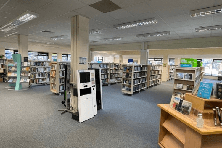 Inside West Kirby Library - view of bookshelves, a self serve kiosk and a new book display.