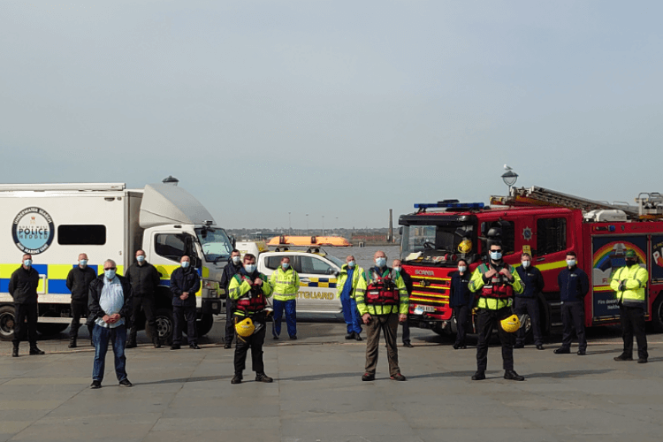 Members of the Merseyside Water Safety Forum standing in front of a fire engine, police van and coastguard vehicle - all wearing face coverings and social distanced.