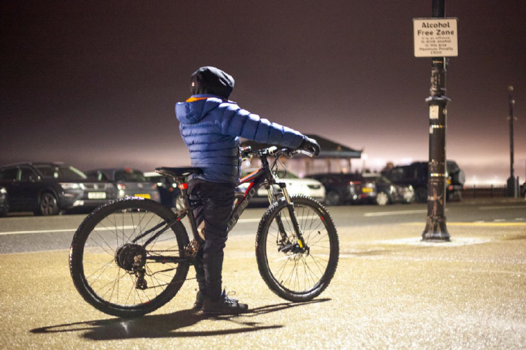 Young person in a blue jacket stands under a streetlight at night, holding the handlebars of a black bike in New Brighton.