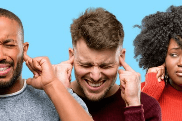 Three people with their fingers in their ears looking in pain.