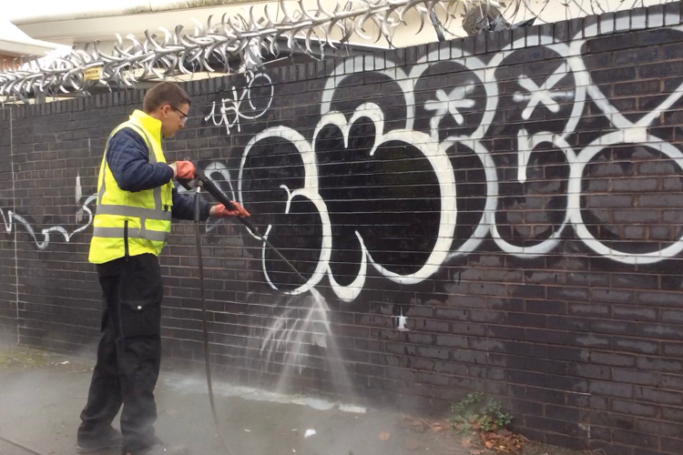 Removing graffiti from a wall