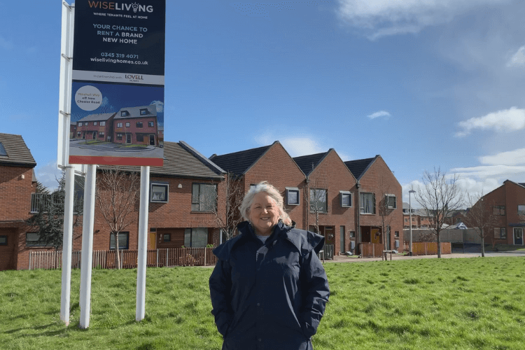 Cllr Julie McManus in front of a row of houses which are part of the Sevenoaks development in Rock Ferry.