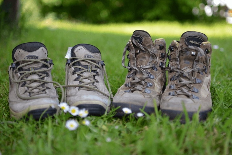 Two pairs of walking boots on a patch of grass