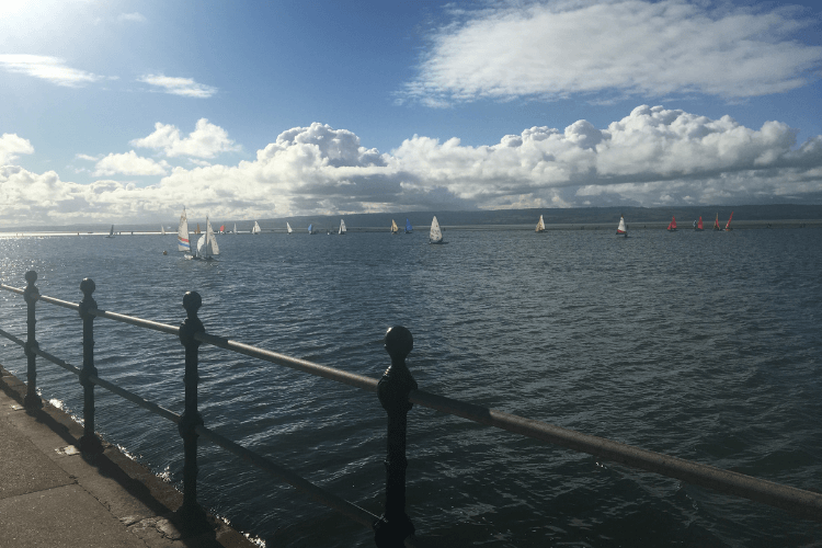 Picture of West Kirby Marine Lake from the promenade with windsurfing and sailing taking place on the water.