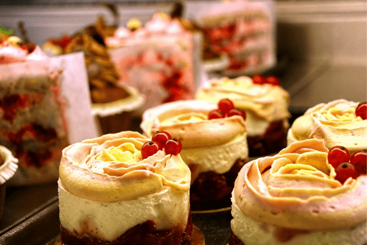 A row of cakes with cream and fruit on top.