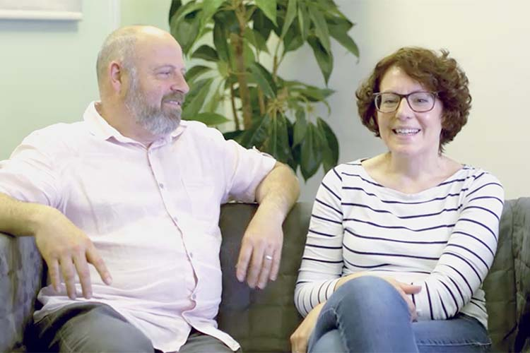Picture of Kate and Adrian, adopters, sitting on a couch.